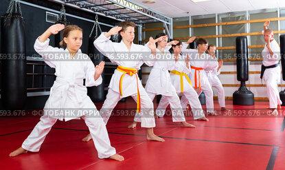 Karate kids in kimono performing kata moves