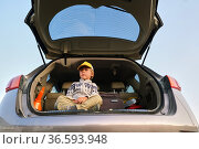 Kid sitting in open car trunk summer journey. Стоковое фото, фотограф Ekaterina Demidova / Фотобанк Лори