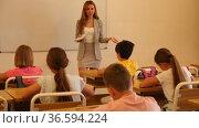 Young smiling woman teacher explaining new theme to children during class in primary school. Стоковое видео, видеограф Яков Филимонов / Фотобанк Лори