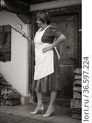Frau im Landhauskleid und Küchenschürze steht vor der Türe ihres ... Стоковое фото, фотограф Zoonar.com/Eder Christa / age Fotostock / Фотобанк Лори