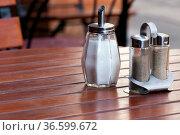 Zuckerspender mit Pfeffergefäßen auf einem Holztisch im Gartenlokal. Стоковое фото, фотограф Zoonar.com/Karl Heinz Spremberg / easy Fotostock / Фотобанк Лори
