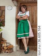 Seniorin im Dirndlkleid steht glücklich vor altem bayrischem Bauernhaus. Стоковое фото, фотограф Zoonar.com/Eder Christa / age Fotostock / Фотобанк Лори