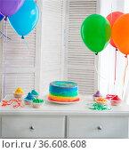 Rainbow cake and cupcakes on the Birthday party. Balloons on the background... Стоковое фото, фотограф Zoonar.com/Dasha Petrenko / easy Fotostock / Фотобанк Лори