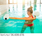 Blond young woman doing aqua aerobics with foam dumbbells in swimming... Стоковое фото, фотограф Zoonar.com/Dasha Petrenko / easy Fotostock / Фотобанк Лори