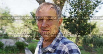 Portrait of smiling caucasian senior man looking at camera outdoors in garden