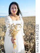 Woman in white dress stands in field with wheat. Person hold in hands... Стоковое фото, фотограф David Herraez Calzada / easy Fotostock / Фотобанк Лори
