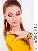 Portrait of young beautiful girl with make up wearing long yellow... Стоковое фото, фотограф Zoonar.com/Dasha Petrenko / easy Fotostock / Фотобанк Лори
