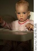 Маленький мальчик сидит за столом для кормления ребенка. Стоковое фото, фотограф Момотюк Сергей / Фотобанк Лори