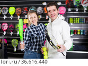 Glad couple choosing padel racket and balls. Стоковое фото, фотограф Яков Филимонов / Фотобанк Лори