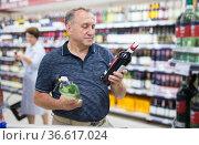 mature man choosing alcoholic drinks in supermarket. Стоковое фото, фотограф Татьяна Яцевич / Фотобанк Лори