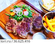 Beef steak with fried potatoes, sauce and arugula at wooden desk. Стоковое фото, фотограф Яков Филимонов / Фотобанк Лори