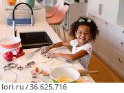 Happy african american messy girl baking in kitchen. Стоковое фото, агентство Wavebreak Media / Фотобанк Лори