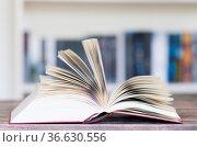 Aufgeschlagenes Buch vor Buecherregal mit fliegenden Buchseiten und... Стоковое фото, фотограф Zoonar.com/Uwe Bauch / easy Fotostock / Фотобанк Лори
