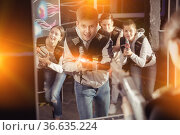 Portrait of happy young man with laser pistol and playing laser tag with his friends in dark room. Стоковое фото, фотограф Яков Филимонов / Фотобанк Лори
