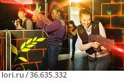 Young man and woman playing laser tag. Стоковое фото, фотограф Яков Филимонов / Фотобанк Лори
