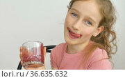 Sweet little girl drinks raspberry smoothie and smiles. Vegetarian drink. Close-up portrait of a child who enjoys a refreshing tasty raspberry juice, healthy eating. Стоковое видео, видеограф Ольга Балынская / Фотобанк Лори