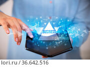 Businessman holding a foldable smartphone with BUSINESS inscription... Стоковое фото, фотограф Zoonar.com/rancz / easy Fotostock / Фотобанк Лори