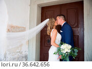 The Kiss. Bride and groom kisses tenderly in front of church portal... Стоковое фото, фотограф Zoonar.com/Matej Kastelic / easy Fotostock / Фотобанк Лори
