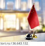 China flag on the reception desk in the lobby of the hotel. Стоковое фото, фотограф Zoonar.com/BUTENKOV ALEKSEY / easy Fotostock / Фотобанк Лори