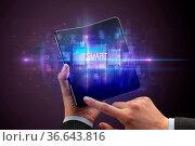 Businessman holding a foldable smartphone with SMART inscription,... Стоковое фото, фотограф Zoonar.com/rancz / easy Fotostock / Фотобанк Лори