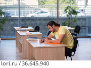 Young male student sitting in the classroom. Стоковое фото, фотограф Elnur / Фотобанк Лори