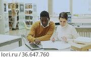 Two adult students studying together in public library. Стоковое видео, видеограф Яков Филимонов / Фотобанк Лори