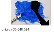 Mid section of silhouette of female handball player against blue paint stain and paint brush. Стоковое фото, агентство Wavebreak Media / Фотобанк Лори