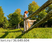 Mature woman in countryside is standing behind a wooden fence serious... Стоковое фото, фотограф Emil Pozar / age Fotostock / Фотобанк Лори
