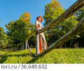 Mature woman in countryside is standing behind a wooden fence laughing... Стоковое фото, фотограф Emil Pozar / age Fotostock / Фотобанк Лори