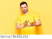 Young displeased man making stop gesture sign say no isolated on yellow... Стоковое фото, фотограф Zoonar.com/Viktor Gladkov / easy Fotostock / Фотобанк Лори