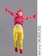 The joyful Child in warm bright clothes bounces. Boy in winter hat... Стоковое фото, фотограф Zoonar.com/Lazarenka Sviatlana / easy Fotostock / Фотобанк Лори