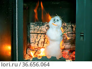 Little snowman melts quickly in hot stove against background of firewood... Стоковое фото, фотограф Zoonar.com/Maximilian Buzun / easy Fotostock / Фотобанк Лори