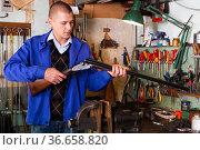 Gunsmith performing checkout of horizontal double rifle in weapons workshop. Стоковое фото, фотограф Яков Филимонов / Фотобанк Лори