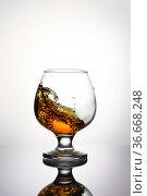 Splash of cognac in glass isolated on a light background. Стоковое фото, фотограф Александр Иванов / Фотобанк Лори