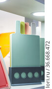 Various plastic cutting boards are stored on a stand on the table. Kitchen utensils and accessories in trendy pastel colors. Стоковое фото, фотограф Светлана Евграфова / Фотобанк Лори