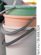 Various plastic new empty buckets stacked. Inventory and household items in trendy pastel colors. Industrial background. Стоковое фото, фотограф Светлана Евграфова / Фотобанк Лори