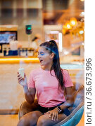Smiling girl eating an ice-cream in a waffle cup in a cafe. Стоковое фото, фотограф Zoonar.com/Oleksii Hrecheniuk / easy Fotostock / Фотобанк Лори