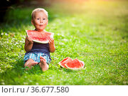 Cute toddler sitting outdoords and eating a slice of watermelon. Стоковое фото, фотограф Zoonar.com/Tomas Anderson / easy Fotostock / Фотобанк Лори