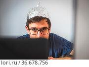 Young man is wearing aluminum cap, conspiracy theory concept. Стоковое фото, фотограф Zoonar.com/Patrick Daxenbichler / easy Fotostock / Фотобанк Лори