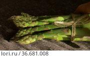 Bunch of fresh green asparagus on dark wooden table, healthy eating, seasonal products. Стоковое видео, видеограф Ольга Балынская / Фотобанк Лори