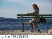 Makarska, Croatia, A tourist sitting on bench by the sea. Стоковое фото, фотограф A. Farnsworth / age Fotostock / Фотобанк Лори
