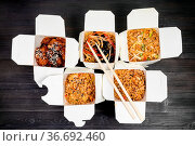 Top view of chinese fast food in disposable cardboard boxes and wooden... Стоковое фото, фотограф Zoonar.com/Valery Voennyy / easy Fotostock / Фотобанк Лори