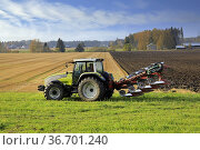 Farmer plowing field with green Valtra tractor and plough on a sunny... (2020 год). Редакционное фото, фотограф Taina Sohlman / age Fotostock / Фотобанк Лори