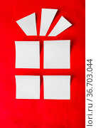 Outline a Christmas gift of a white paper on a red background. Стоковое фото, фотограф Zoonar.com/Lyubov Pimenova / age Fotostock / Фотобанк Лори