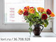 Bouquet of fresh red and yellow rose flowers in ceramic jug on window... Стоковое фото, фотограф Zoonar.com/Valery Voennyy / easy Fotostock / Фотобанк Лори