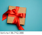 Square gift box is packed in red paper and curled red silk ribbon... Стоковое фото, фотограф Zoonar.com/Danko Natalya / easy Fotostock / Фотобанк Лори