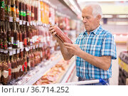 mature senor choosing uncooked smoked sausages in sausage department supermarket. Стоковое фото, фотограф Татьяна Яцевич / Фотобанк Лори