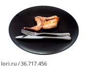 Half of fried quail on black plate with fork and knife isolated on... Стоковое фото, фотограф Zoonar.com/Valery Voennyy / easy Fotostock / Фотобанк Лори