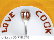 Love to cook written by tomato sauce on white plate and silver spoon. Стоковое фото, фотограф Zoonar.com/Yury Zap / easy Fotostock / Фотобанк Лори
