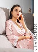 Bored woman sitting on a sofa in the living room. Стоковое фото, фотограф Яков Филимонов / Фотобанк Лори
